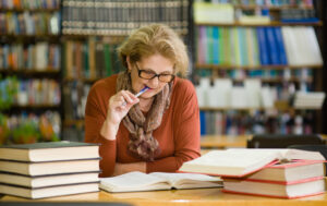 Woman chewing pencil studying for exam